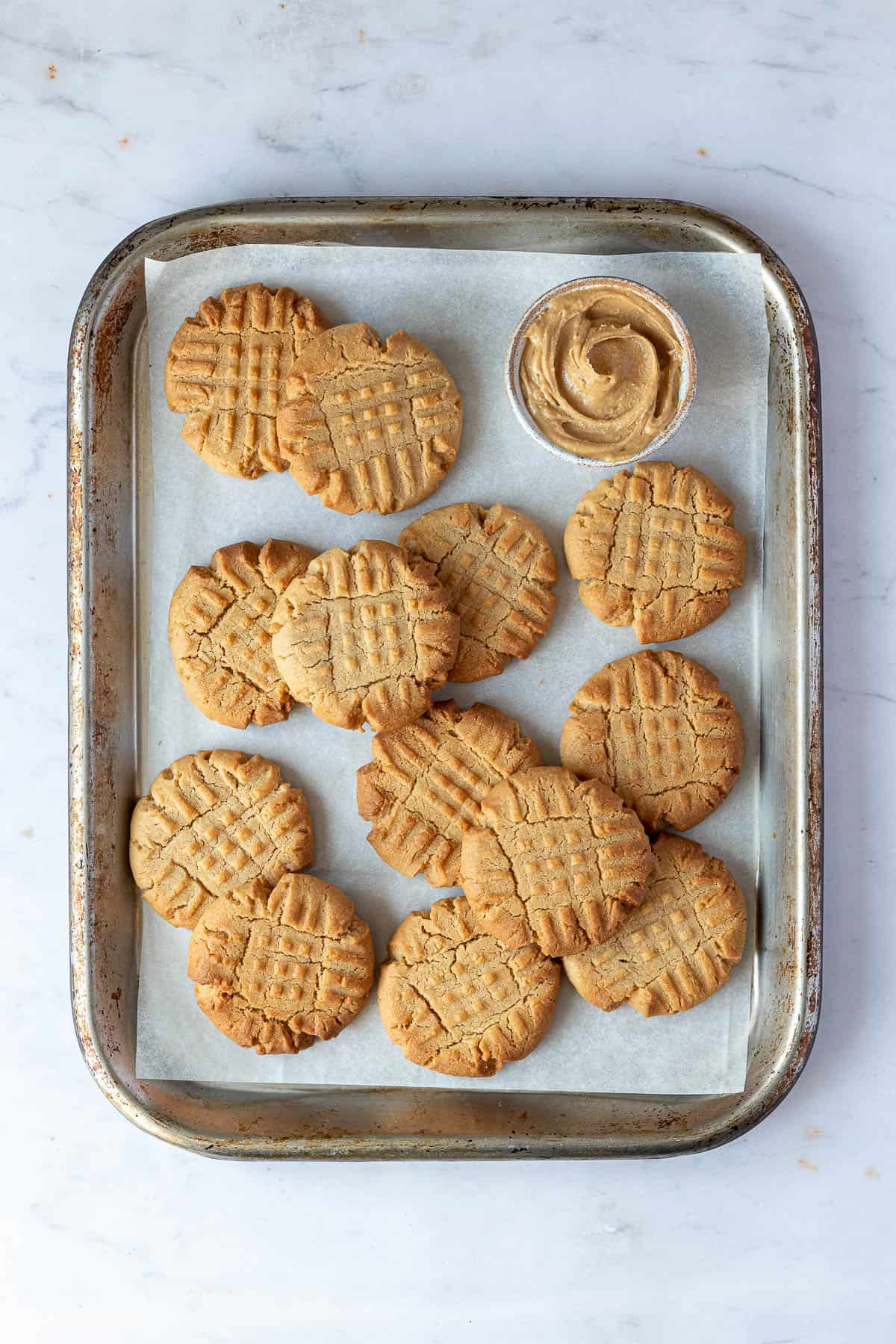 Vegan peanut butter cookies with a bowl of peanut butter on a metal baking sheet.