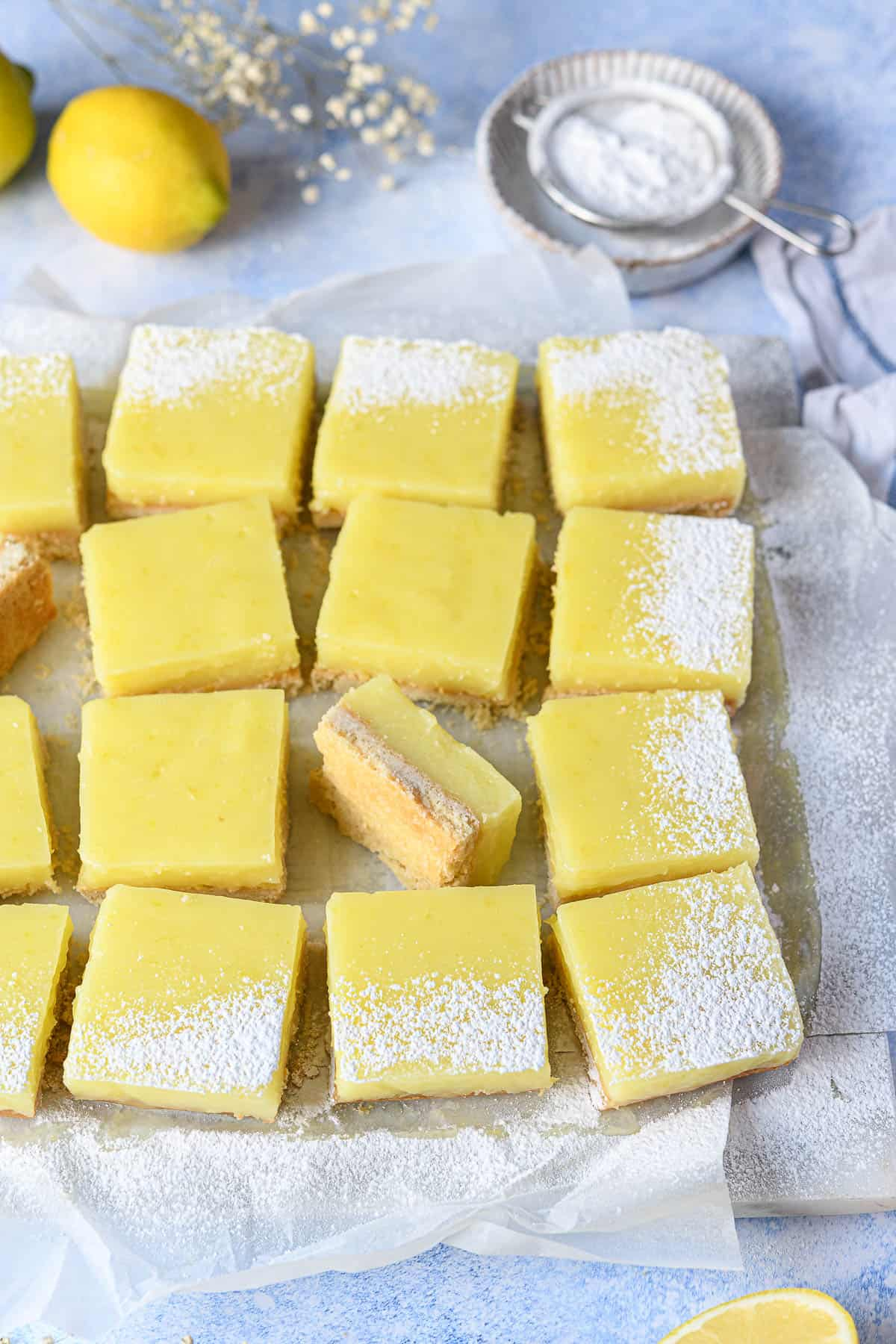 Lemon bars on white baking parchment on a blue surface.