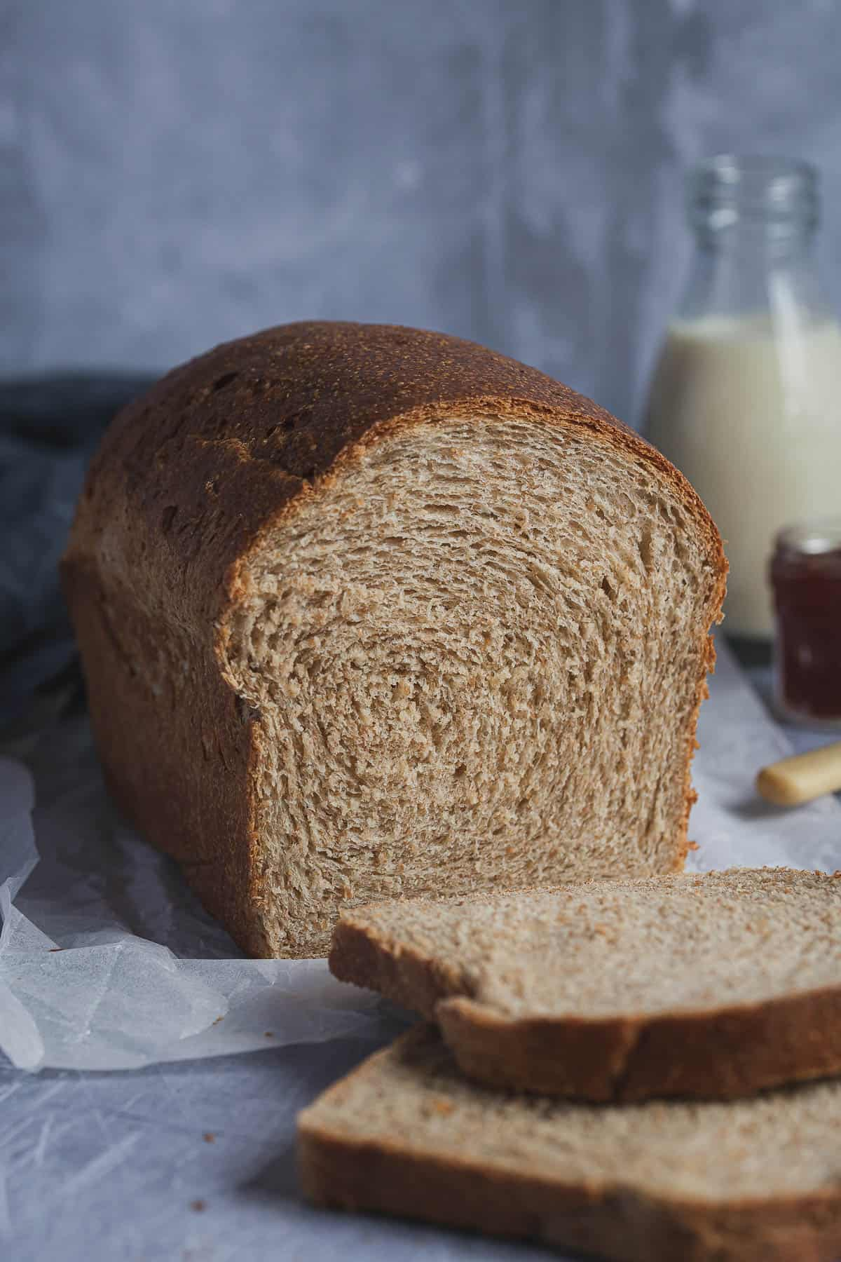 A loaf of vegan wholemeal sandwich bread with two slices cut off and a bottle of milk and jar of jam in the background.