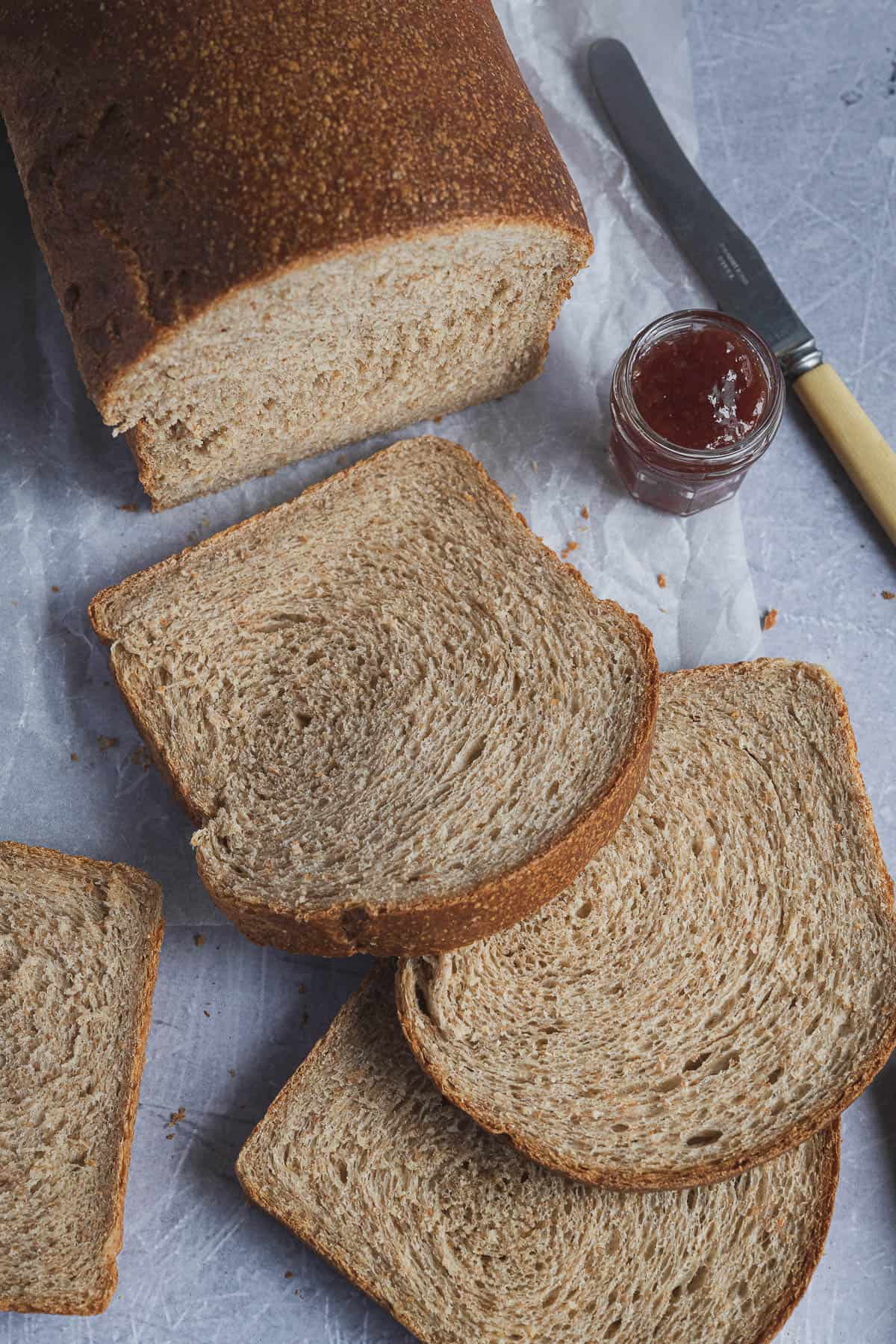 Sliced wholemeal sandwich bread on a sheet of white baking parchment with a jar of jam and a knife.
