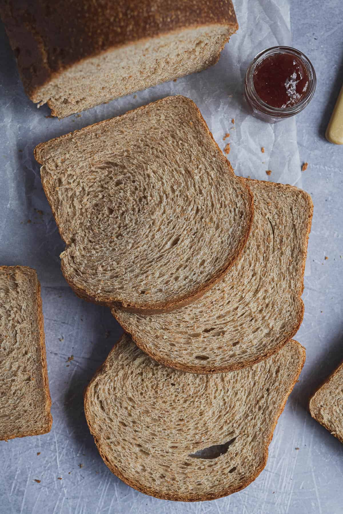 Slices of vegan wholemeal sandwich bread with a jar of jam.