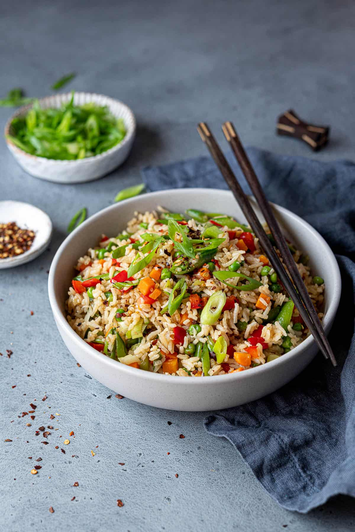 A bowl of vegetable fried rice with chopsticks, a bowl of spring onions and a bowl of chilli flakes.