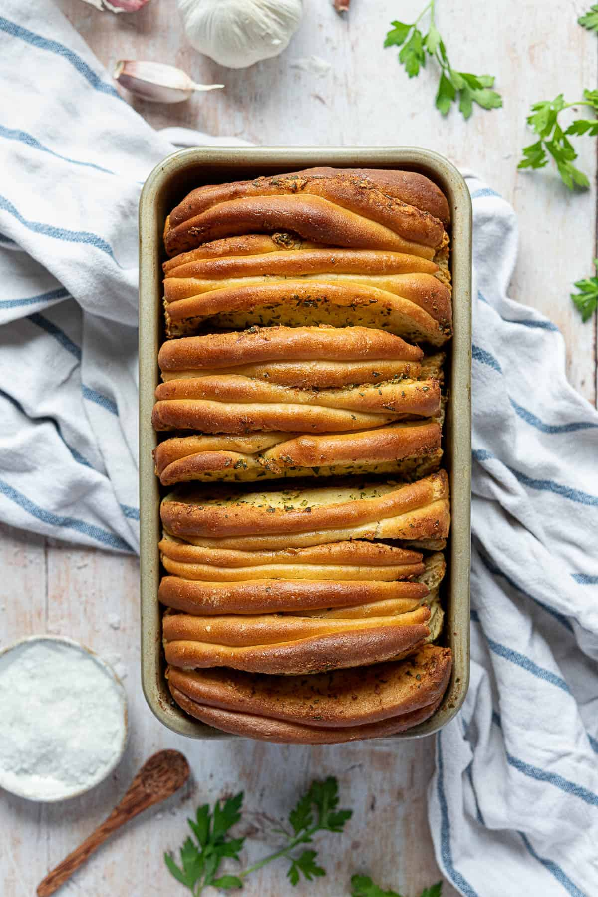 Vegan garlic pull apart bread in a loaf tin on a wooden table with a blute and white tea towel, fresh garlic, parsley and a bowl of salt.