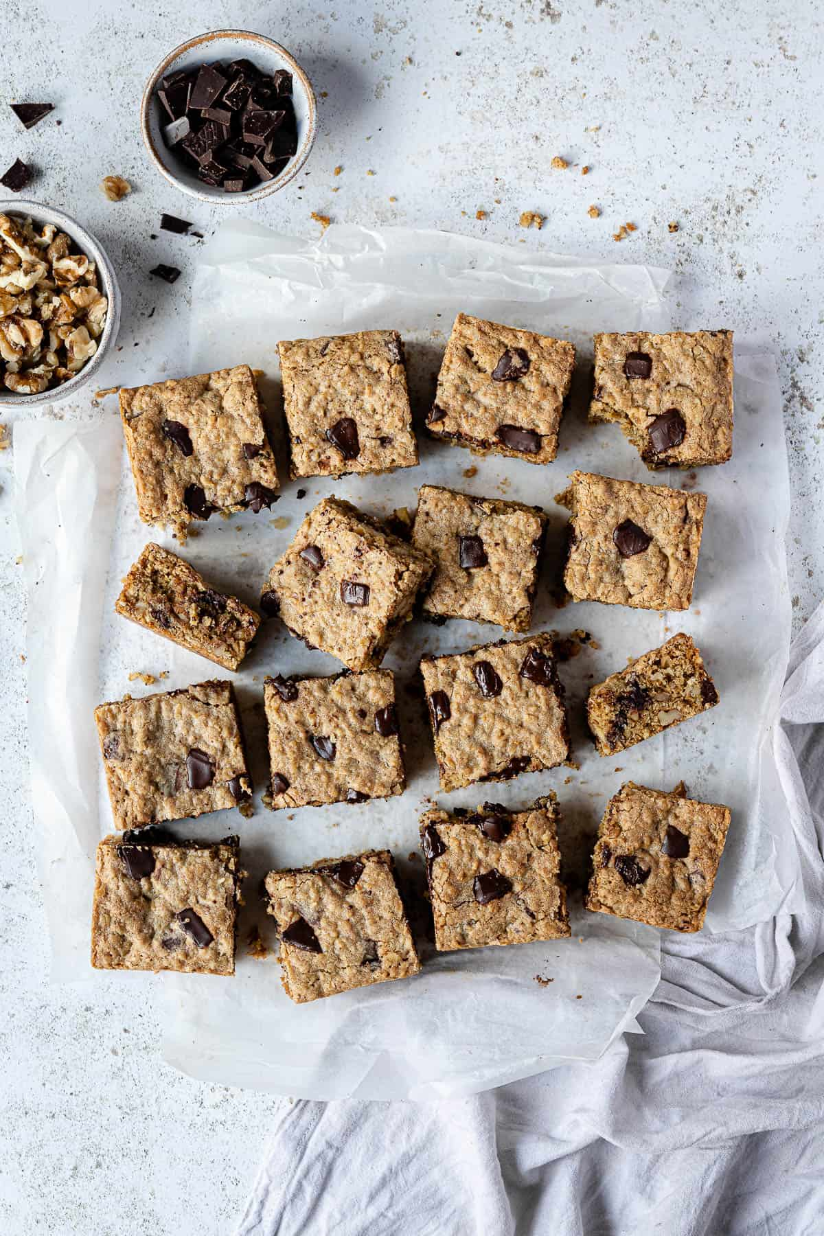 Oatmeal cookie bars on a sheet of baking parchment on a white surface with bowls of chocolate and walnuts and a grey cloth.