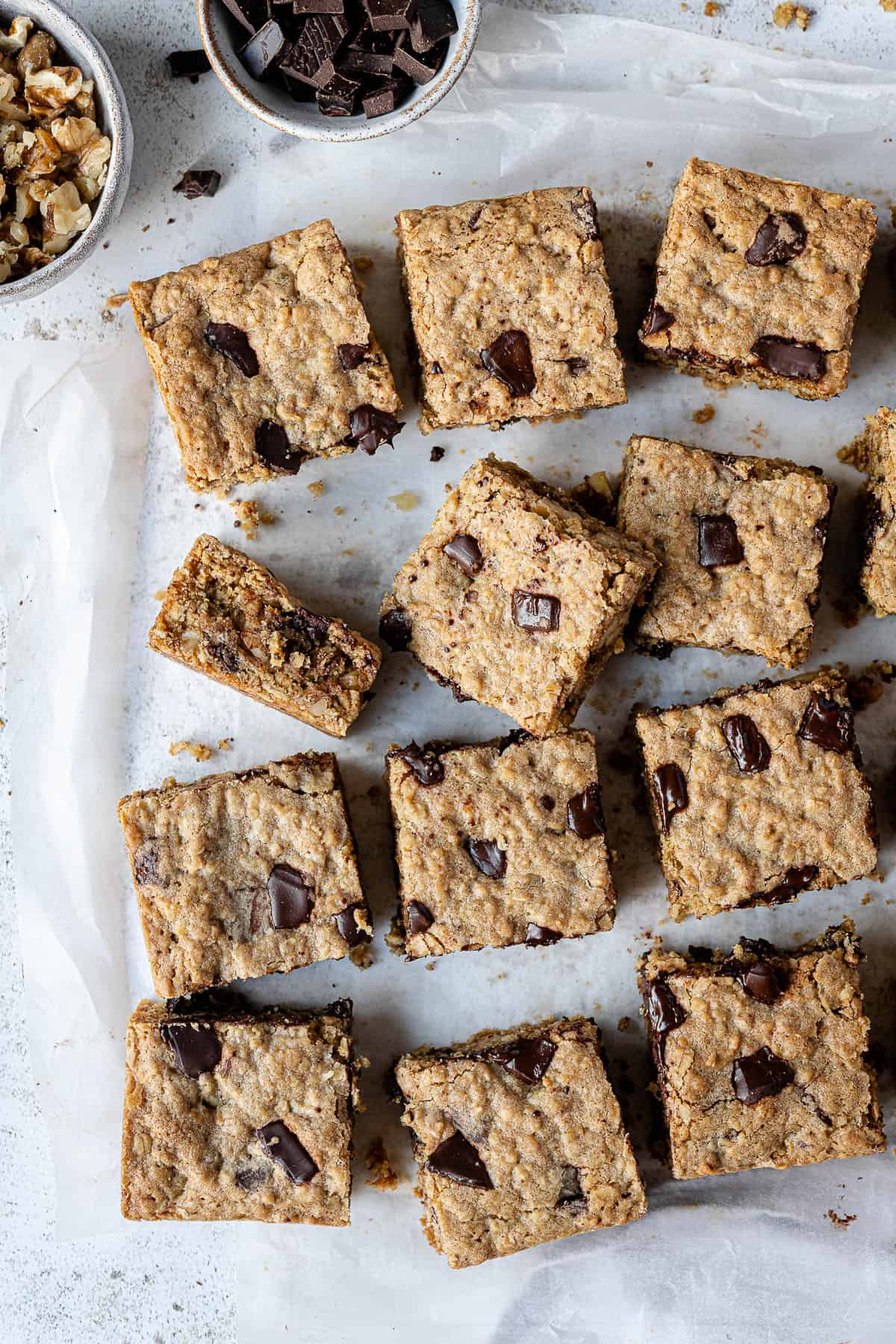 Vegan oatmeal cookie bars on a sheet of baking parchment with a bowl of walnuts and a bowl of chopped chocolate.