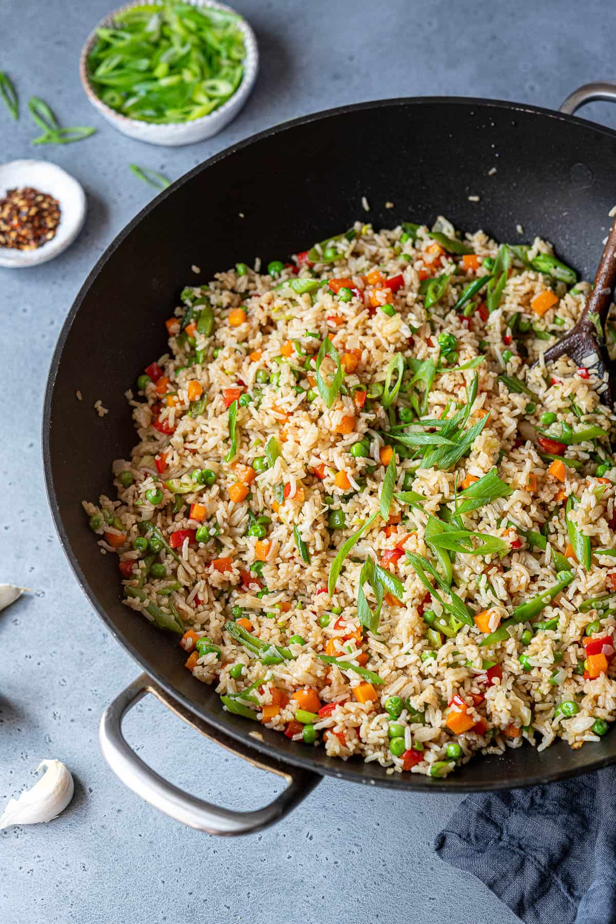 Vegetable fried rice in a wok with a bowl of spring onions and a bowl of chilli flakes.