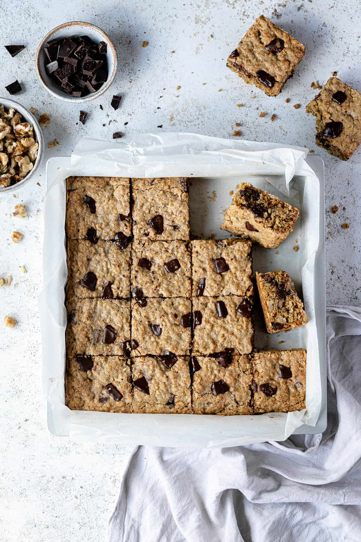 Vegan oatmeal cookie bars in a parchment lined metal tin with a bowl of walnuts and a bowl of chocolate.