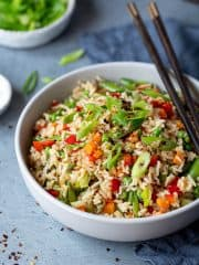 Close up of a bowl full of vegetable fried rice.