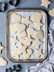 Vegan vanilla sugar cookies on a meatl baking tray with cookie cutters and a grey cloth.