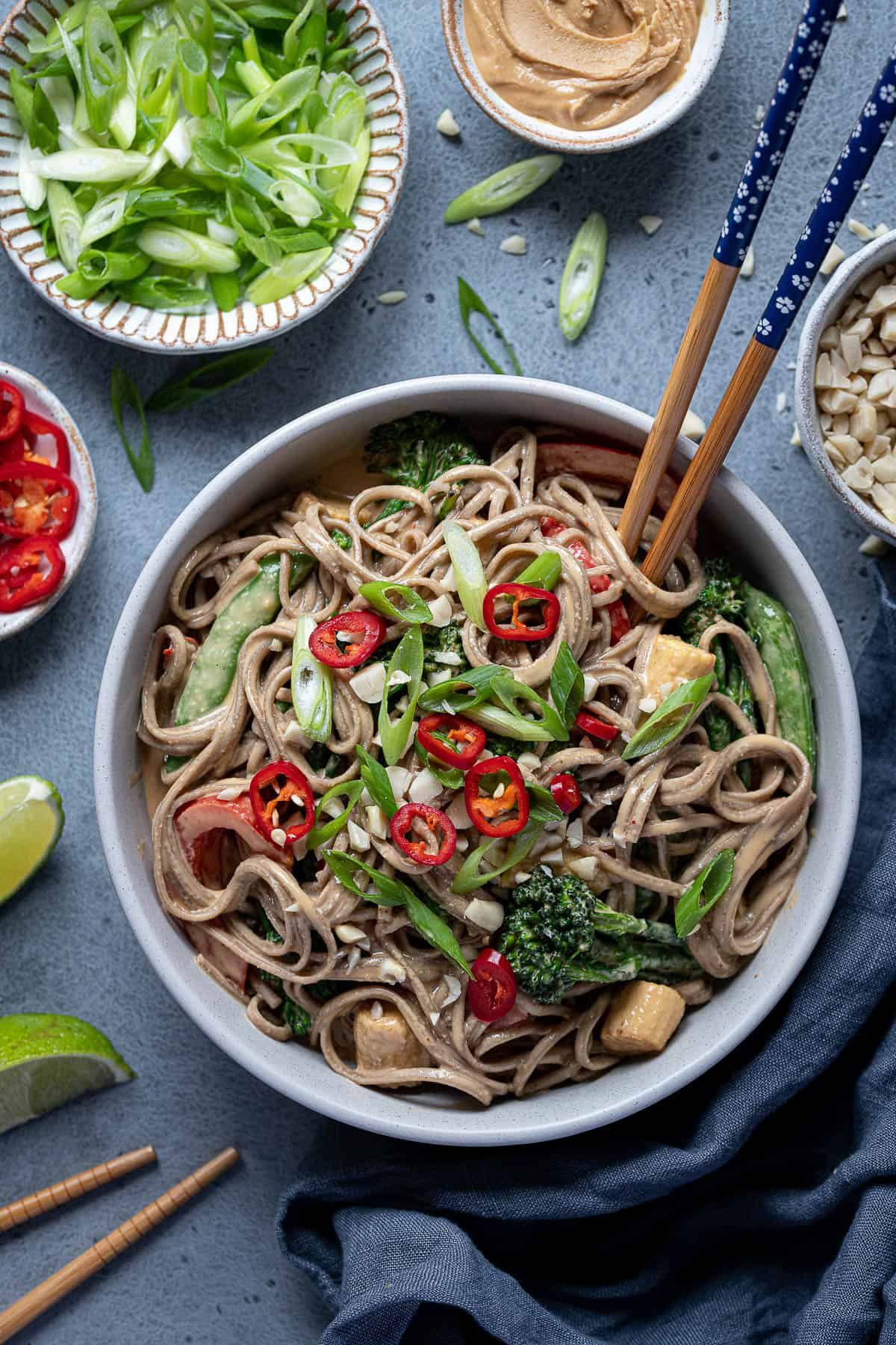 Creamy peanut noodles with stir fried vegetables in a bowl with chopsticks and bowls of spring onions, peanut butter and chillies.