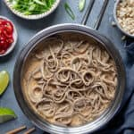 Creamy peanut noodles in a pan with bowls of chopped peanuts, spring onions, chillies and limes.