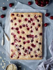 Vegan cherry almond cake on a sheet of baking parchment with bowls of cherries and flaked almonds.