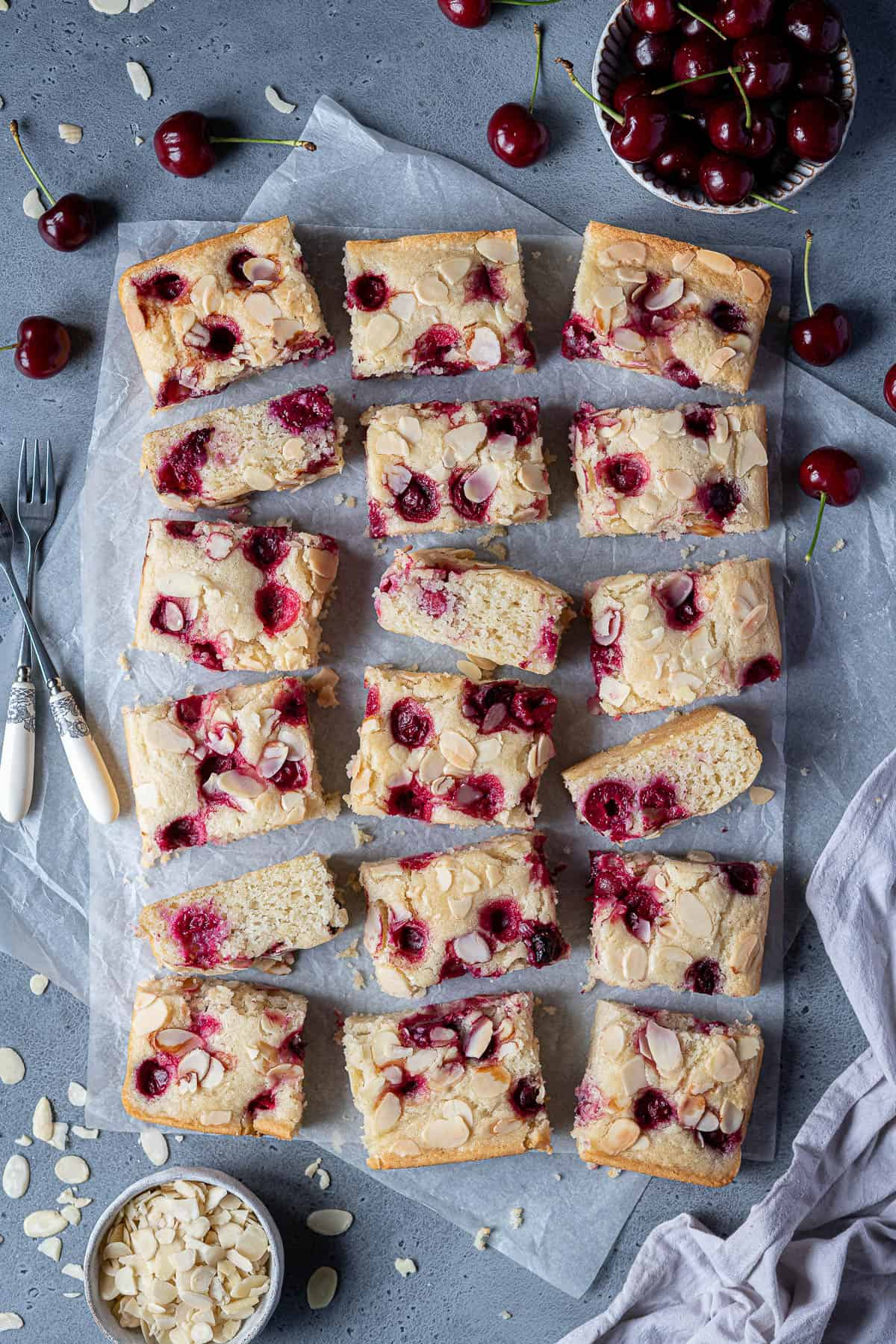 Vegan cherry almond cake cut into squares on a sheet of baking parchment.