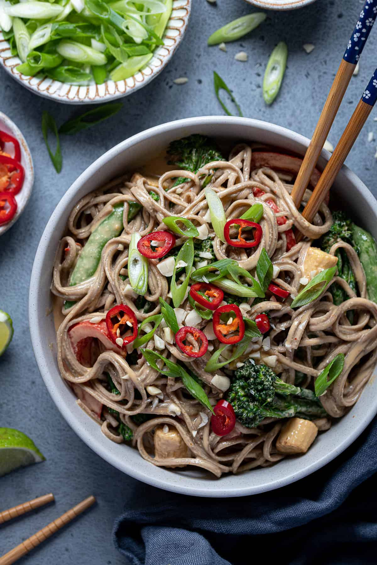 Close up of creamy peanut noodles and vegetables in a bowl with chopsticks, sliced spring onions and chillies.