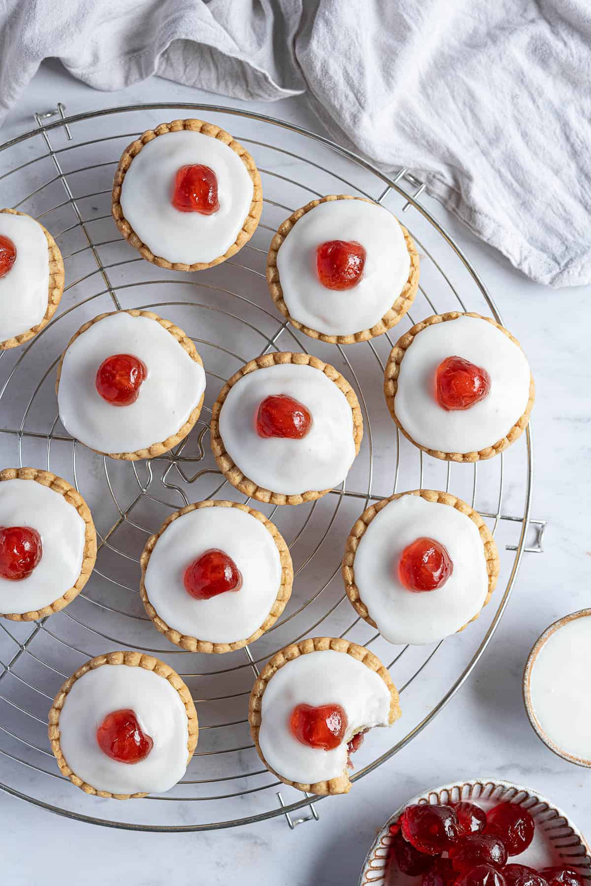 Vegan cherry Bakewells on a round wire cooling rack.
