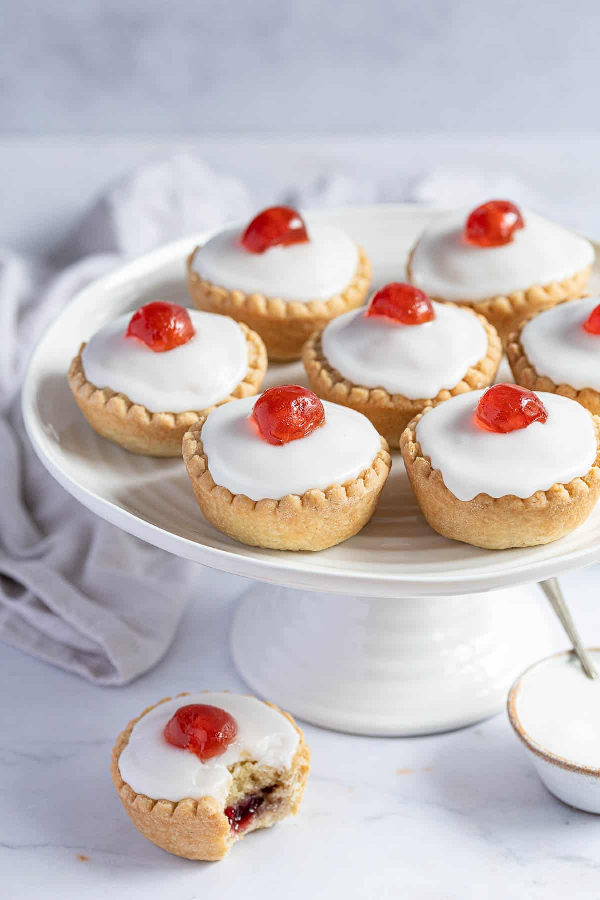 Vegan cherry Bakewells on a white cake stand.
