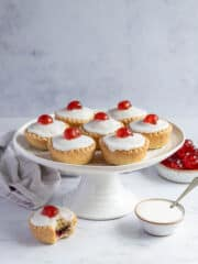 Vegan cherry Bakewells on a white cake stand with a grey cloth, bowl of icing and bowl of glace cherries.