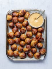 A tray of vegan pretzel bites with a bowl of dipping sauce on a marble background.