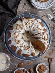 Vegan pumpkin bundt cake on a metal plate with bowls of maple glaze, pecans and pumpkin spice.