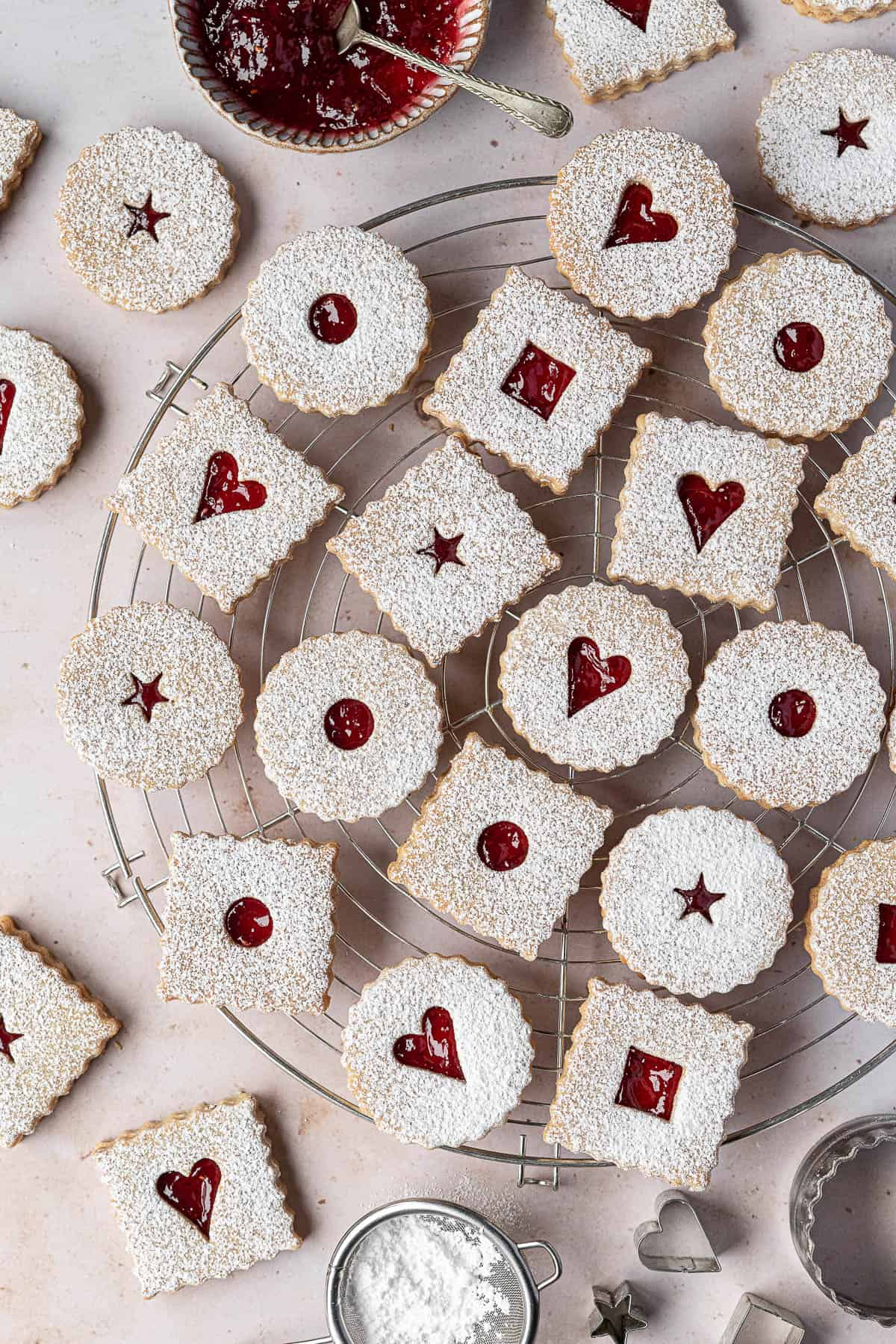 Vegan Linzer cookies on a round wire cooling rack with a bowl of jam, sieve of icing sugar and cookie cutters.