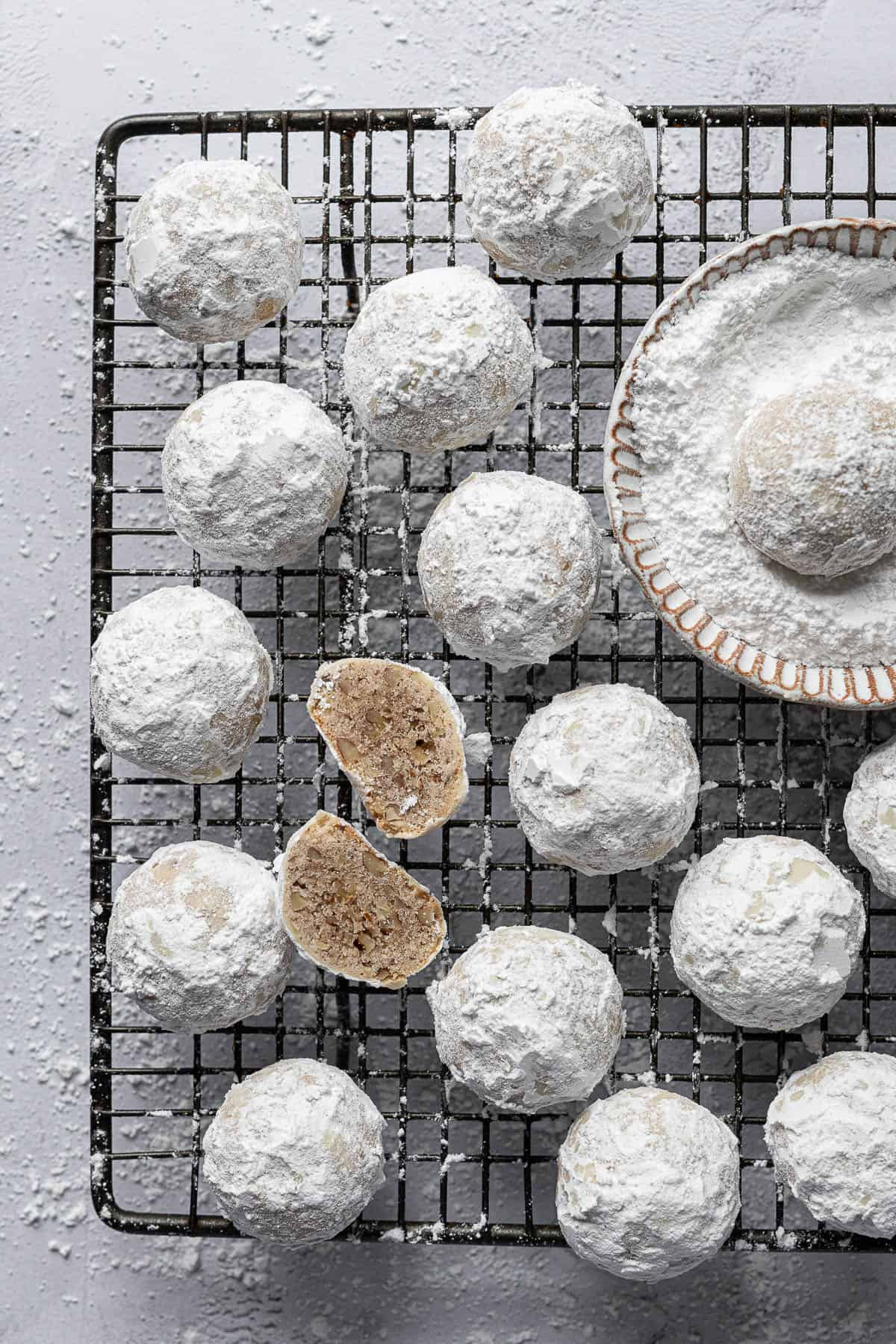 Vegan pecan snowball cookies on a wire rack with a bowl of powdered sugar, one cookie sliced in half.