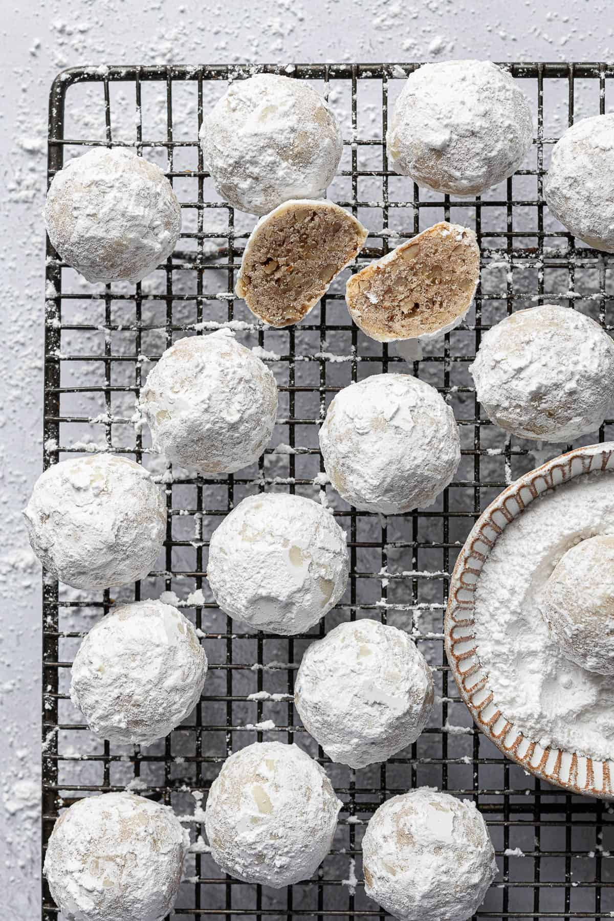 Pecan snowball cookies on a wire rack with a bowl of icing sugar, one sliced in half.