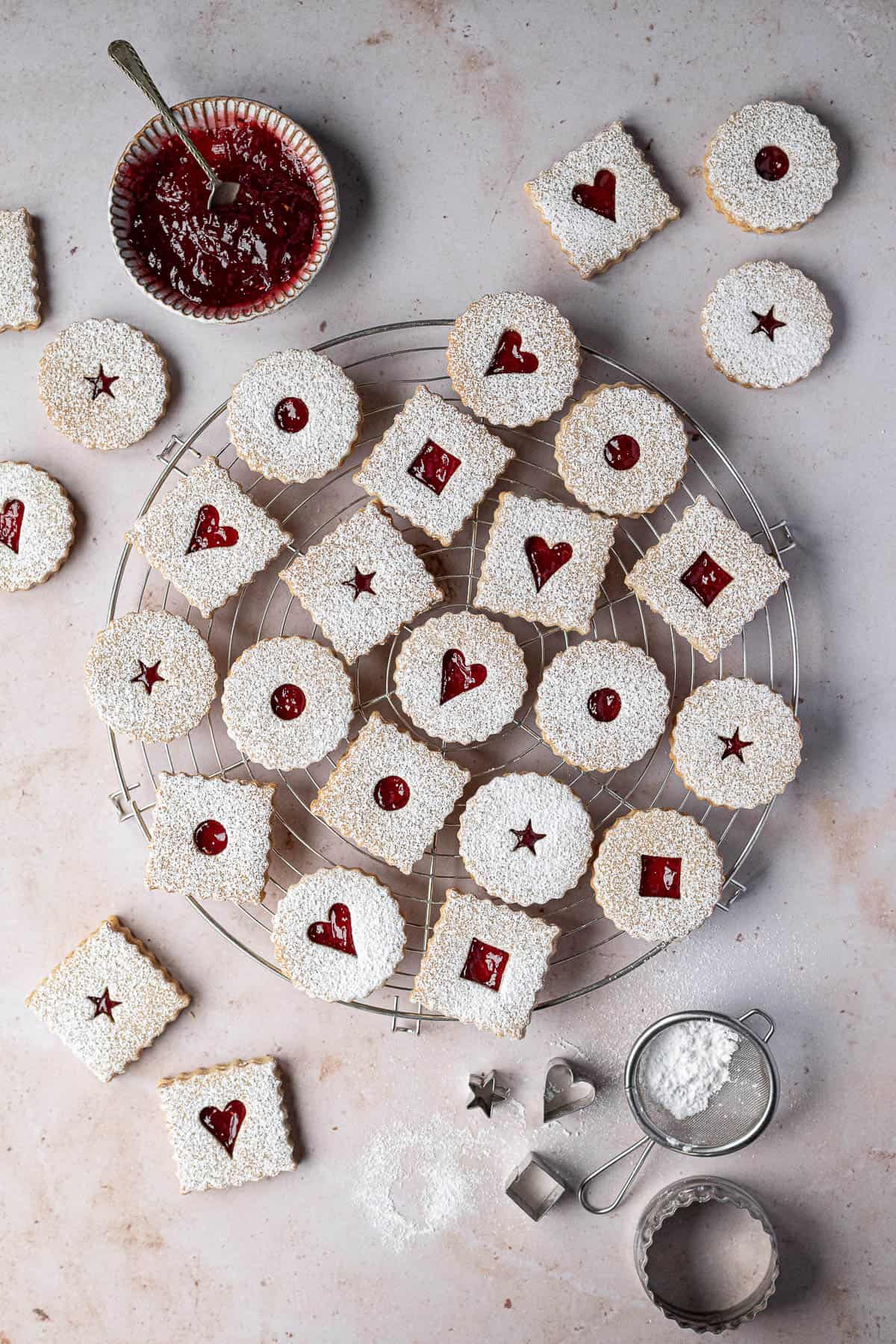 Vegan Linzer cookies on a round wire cooling rack on a marble background with a bowl of jam, mini sieve of icing sugar and cookie cutters.