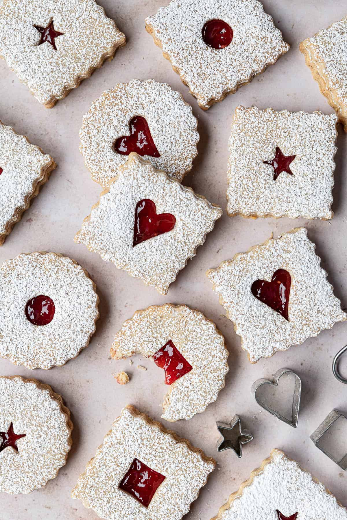 Vegan Linzer cookies on a marble background, one with a bite taken out of it.