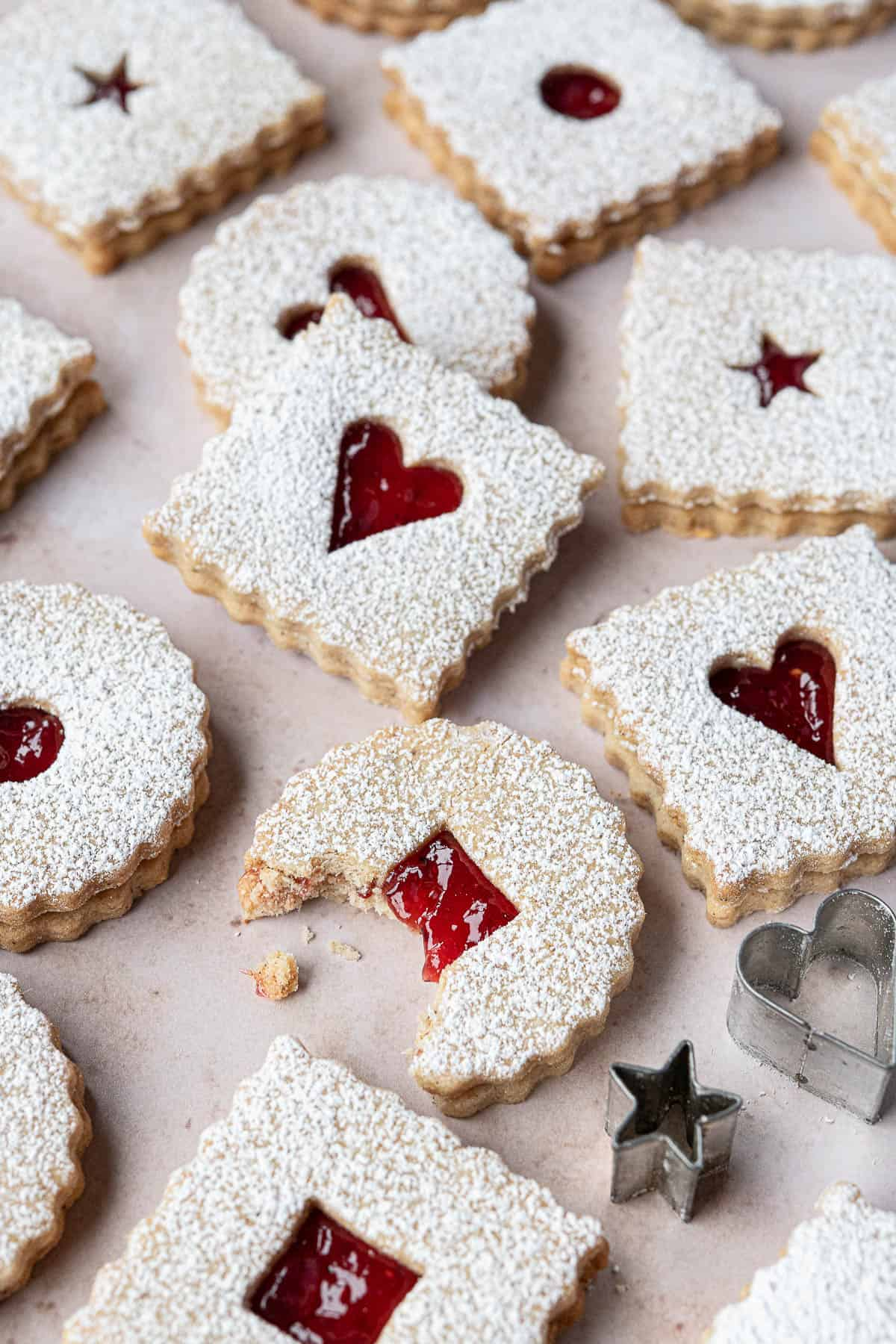 Close up of a Linzer cookie with a bite taken out of it.