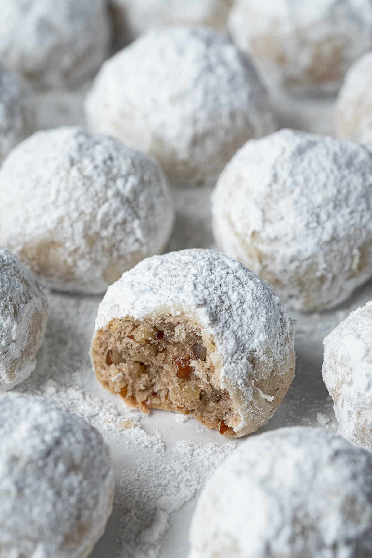 Close up of a vegan pecan snowball cookie with a bite taken out of it.