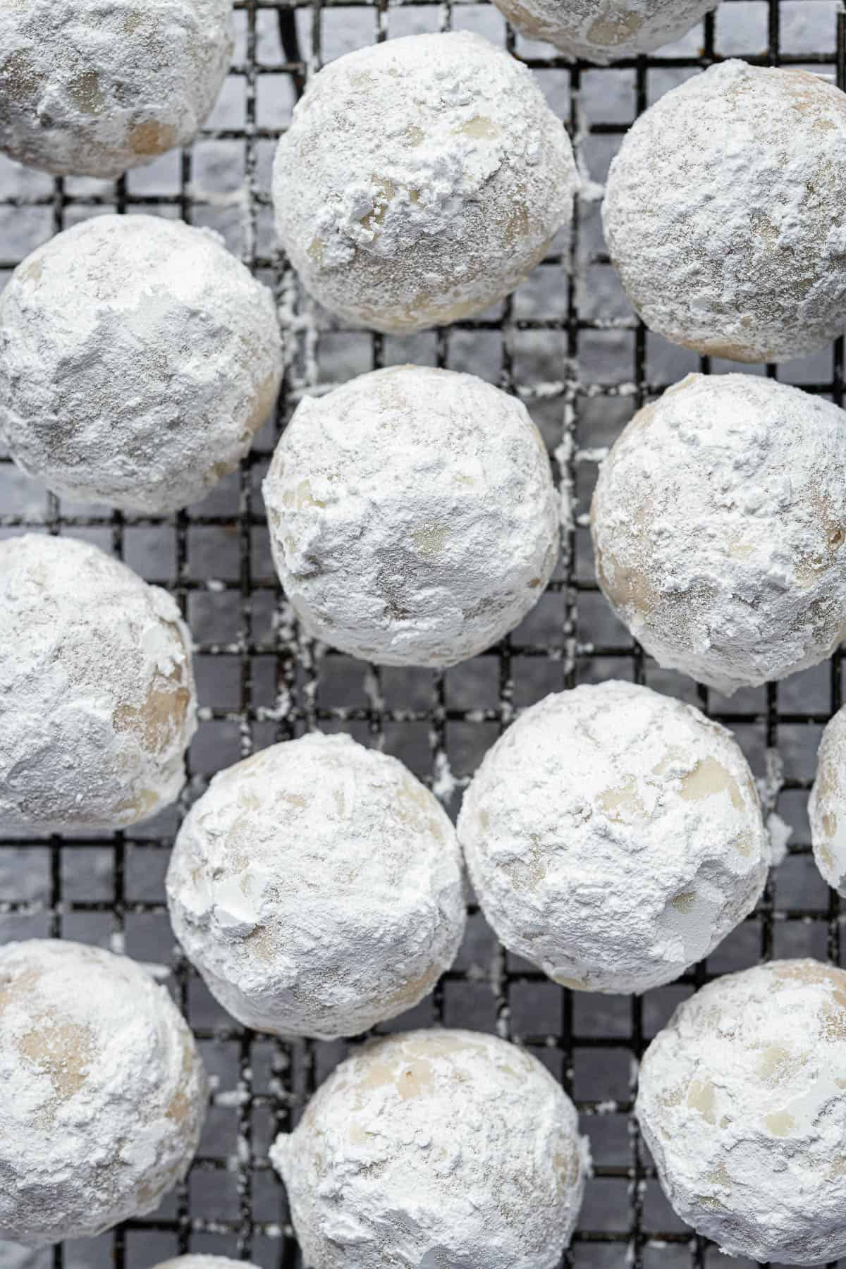 Snowball cookies on a wire rack.