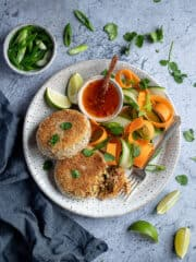 Two vegan Thai red curry fish cakes on a plate with vegetable ribbons and a bowl of sweet chilli sauce, surrounded by lime slices, sliced spring onions and fresh coriander.